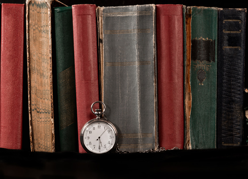 Pocket watch against the number of standing books  .